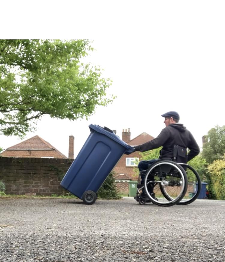 Wheelchair user brining bin in